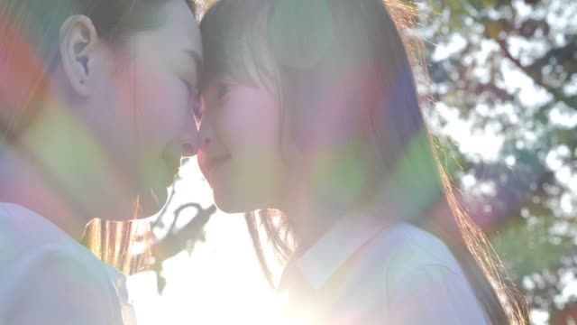 lifestyle of mom and daughter in happiness at the outside in the field at sunset light,kissing and hugging happy family. happy mother's day joy.relaxed parenting - mother and daughter making out stock videos & royalty-free footage