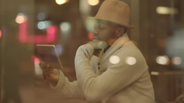 lifestyle portrait of young black man using digital tablet computer browsing the web online - hand on chin stock videos & royalty-free footage