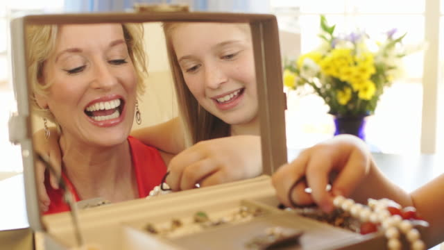 vídeos y material grabado en eventos de stock de lift up shot of grandmother and granddaughter playing with jewellery together indoors. - 50 54 años