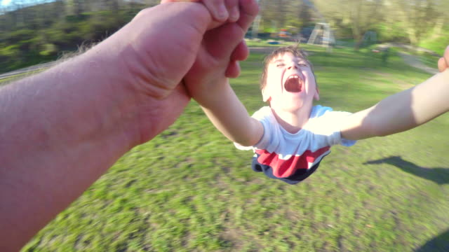 vídeos de stock e filmes b-roll de lifting and spinning his son in the air - ecstatic