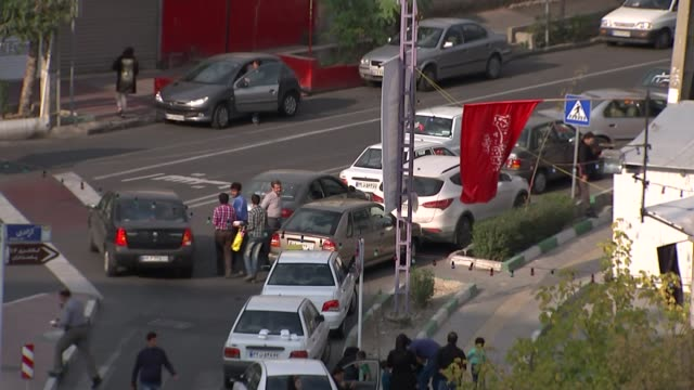 lifting of trade sanctions with iran high angle people crossing road and traffic along young iranian men on street high angle shot buildings and... - 制裁点の映像素材/bロール