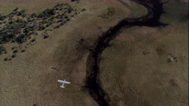 vídeos y material grabado en eventos de stock de a light aircraft flies over a river in the okavango delta. available in hd. - delta de okavango
