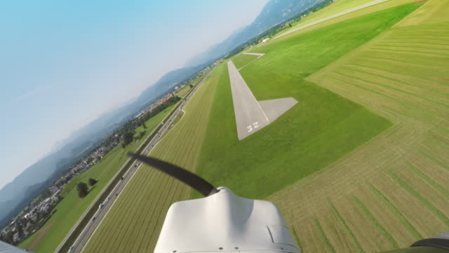 ld light aircraft landing on the grass along the airstrip - propeller stock videos & royalty-free footage