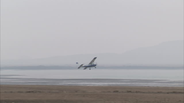 a light aircraft takes off from a beach. available in hd. - luftfahrtindustrie stock-videos und b-roll-filmmaterial