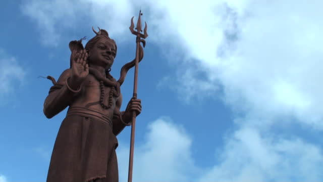 Light and shade play on big Shiva statue against sky