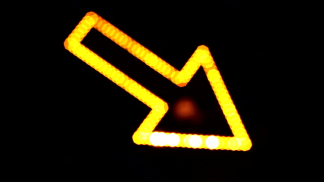 Light arrow, directional sign, light reflection, city lights.