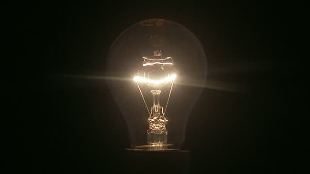 a light bulb being switched on. - light bulb stock videos and b-roll footage