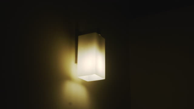 light bulb hanging on the wall turning off. - compact fluorescent light bulb stock videos & royalty-free footage