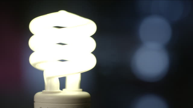 a cfl light bulb is twisted in and out of a socket, switching on and off. - twisted stock videos & royalty-free footage