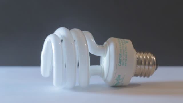 light bulb on black and white background - compact fluorescent light bulb stock videos & royalty-free footage