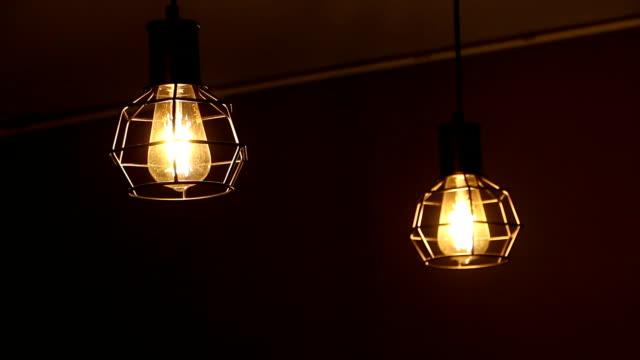 電球カフェで黒の背景に。孤独な気分。 - 一つ点の映像素材/bロール