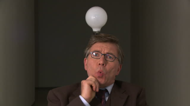 CU Light bulb turning on above head of mature businessman as he gets idea / Berlin, Germany