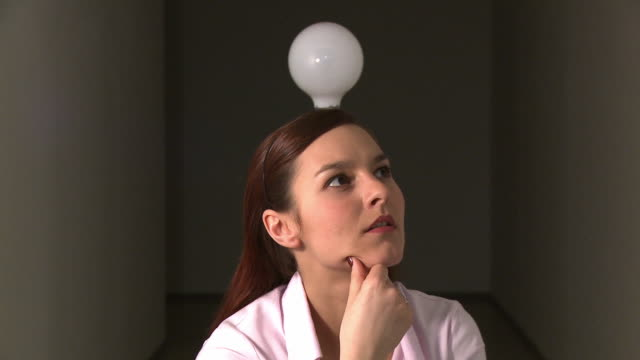 CU Light bulb turning on above head of woman as she gets idea / Berlin, Germany