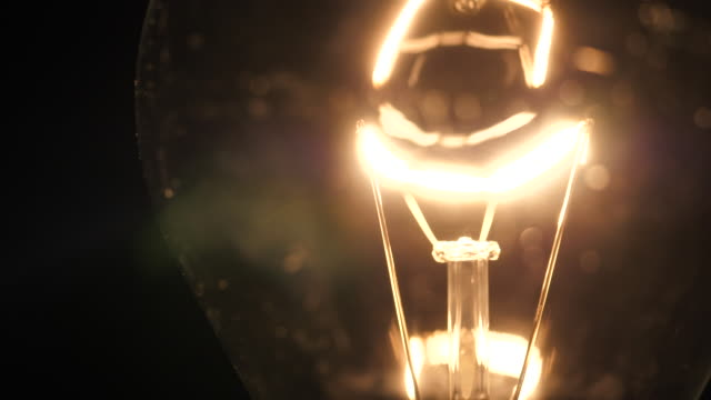 light bulbs illuminate a dark room - electric lamp stock videos & royalty-free footage