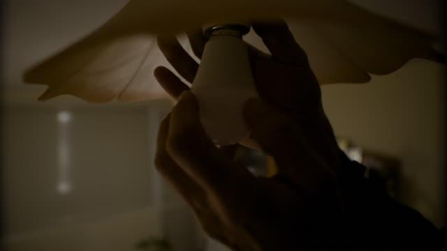led-licht. nahaufnahme der hände eines elektrikers beim wechseln einer glühbirne. engineering, erfahrener profi bei der arbeit. - led leuchtmittel stock-videos und b-roll-filmmaterial
