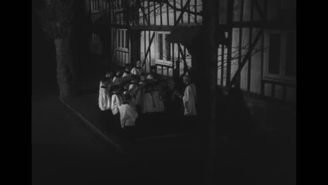 light coming from church windows, church silhouetted against night sky / boys choir in robes carrying sheet music walk towards camera two by two out... - documentary footage stock videos & royalty-free footage