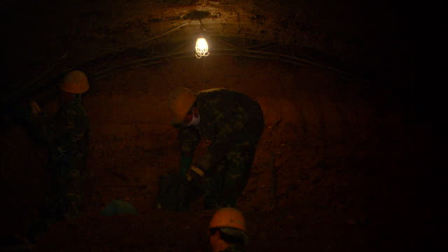 a light dimly illuminates a tunnel of the beijing subway system where construction workers excavate. - real time stock videos & royalty-free footage