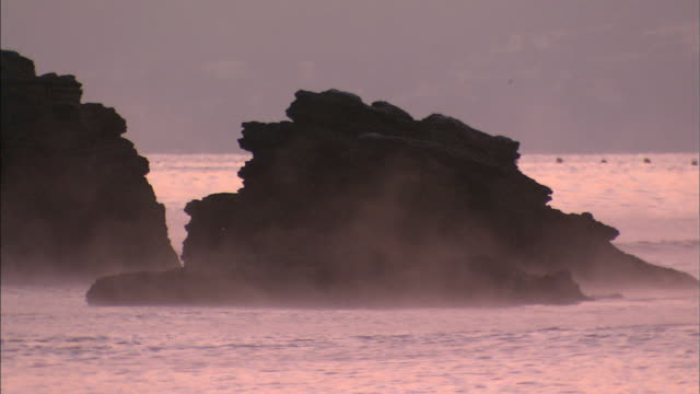 a light fog moves across rocky outcroppings as sunrise casts a pink glow on the sea of japan. - toyama prefecture stock videos and b-roll footage