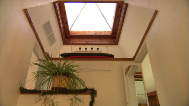 vídeos de stock e filmes b-roll de light from a skylight illuminates the interior of a pyramid-shaped home. - claraboia