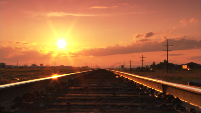 vidéos et rushes de light from a sunset gleams off the rails of a train track as it disappears into the horizon. - voie ferrée