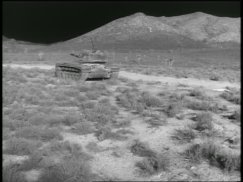 vídeos de stock, filmes e b-roll de b/w 1955 light from atomic bomb explosion on tank in desert with hill in background / nevada / documentary - bomba de hidrogênio