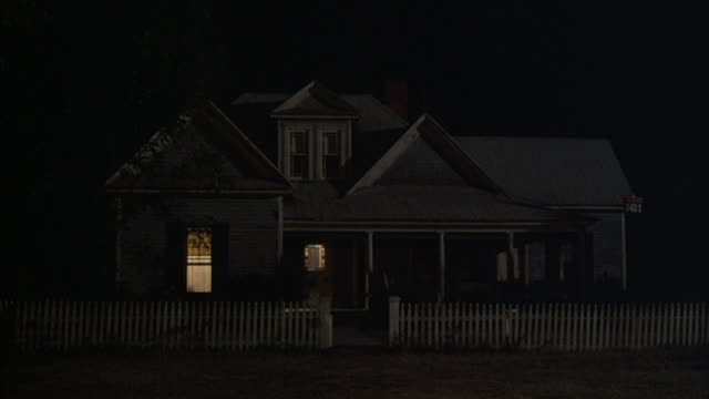 light from within a farm house illuminates the windows at night. - farmhouse stock videos & royalty-free footage