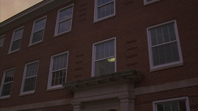A light glows in one of the windows of a brick building.