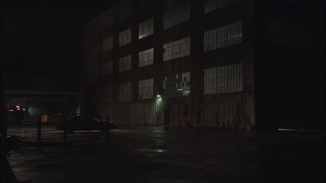 Light glows through the windows of a warehouse.