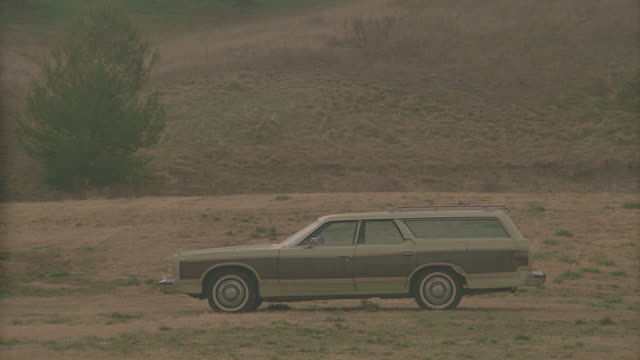 light green wood panel ford station wagon explodes in open field - acrobazia video stock e b–roll