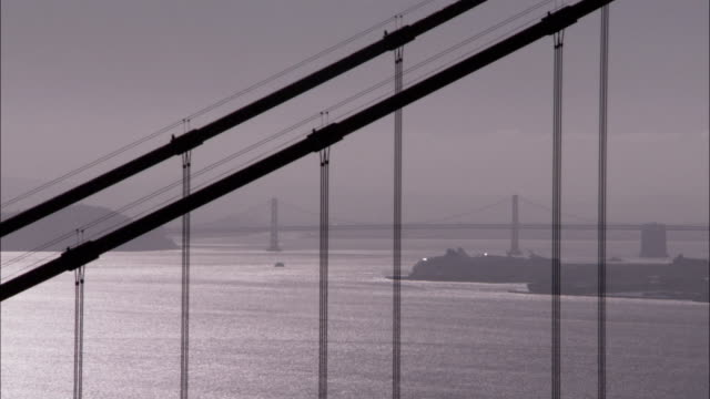 a light haze hovers over san francisco bay and the golden gate bridge. available in hd. - golden gate bridge stock-videos und b-roll-filmmaterial