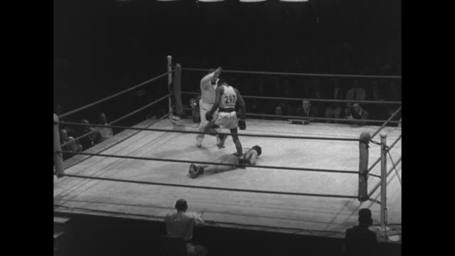 light heavyweight boxers begin match referee in ring / maybe american norvel lee knocks out maybe argentine antonio pacenza / referee stands by... - 一等賞点の映像素材/bロール