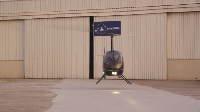 light helicopter landing in front of hangars, enters frame left, red r3d 4k - 飛行機格納庫点の映像素材/bロール