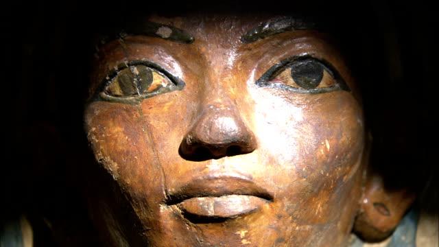 light illuminates a carved face on an ancient egyptian sarcophagus. - 古代の遺物点の映像素材/bロール