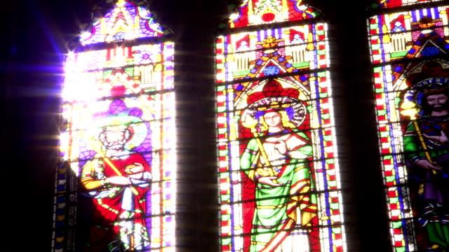 vídeos y material grabado en eventos de stock de light illuminates a stained glass window in the ely cathedral. available in hd. - vidriera de colores