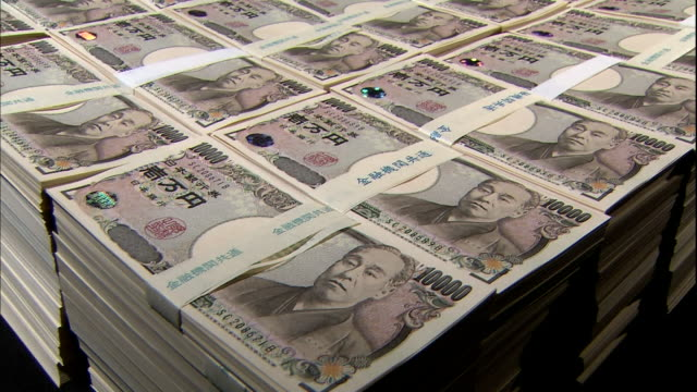 A light illuminates bundles of ten thousand yen bills on a black background in Tokyo, Japan.