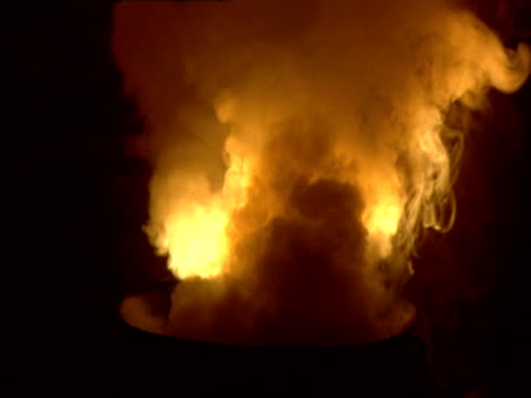 A light illuminates smoke rising from a cauldron.