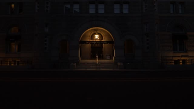 light illuminates the outside of an entrance to trump international hotel on 12th street during the coronavirus pandemic on april 2, 2020 in... - maryland stato video stock e b–roll