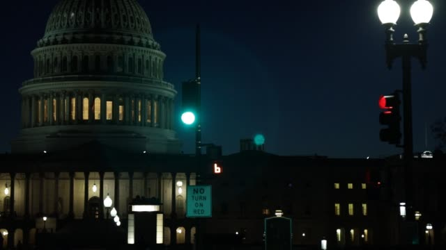 vidéos et rushes de light illuminates the us capitol as streets remain empty of much traffic or pedestrians on capitol hill during the coronavirus pandemic on april 2... - maryland état