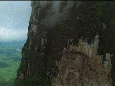 vídeos de stock e filmes b-roll de light mist hovers near the sheer cliff of tepui. - forma de água