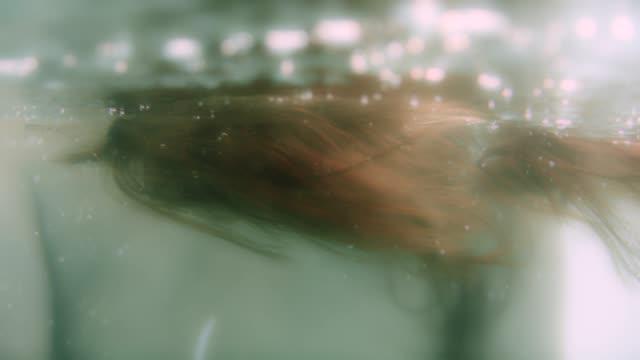 vidéos et rushes de lumière se déplaçant sur les cheveux bruns brillants sous l'eau - brown hair
