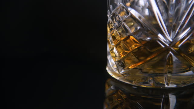 light moving over cut glass tumbler filled with scotch whiskey - cut video transition stock videos & royalty-free footage