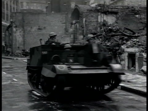 Light open top two man tank moving down street passing bombed building Soldiers infantry holding rifles running on bombed deserted street Soldiers...