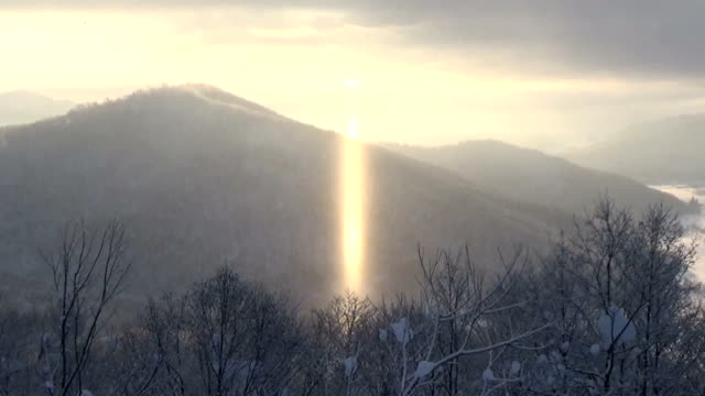 vídeos de stock e filmes b-roll de a light pillar a natural phenomenon that appears when the sun lights reflex where vapors in the air froze during midwinter dawns was seen in japan in... - column