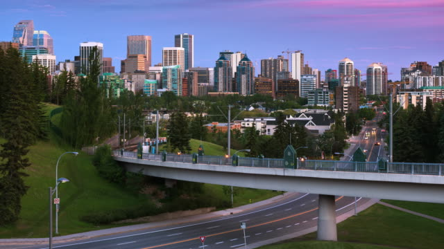 T/L Light rail trains also known as C-Train passes above car traffic with Calgary's skyline in the background after sunset / Calgary, Alberta, Canada