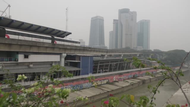 A Light Rail Transit train arrives Pasar Seni LRT station as buildings in the background stand shrouded in haze in Kuala Lumpur Malaysia on Monday...