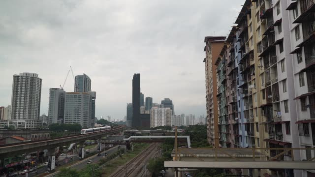 A Light Rail Transit train travels along an elevated track as residential apartment buildings stand in Kuala Lumpur Malaysia on Wednesday Aug 2...