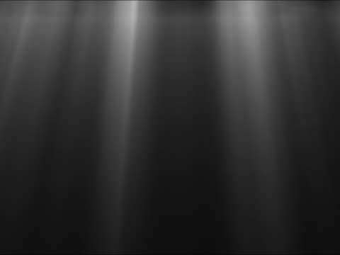 light rays shining on black background - fascio di luce video stock e b–roll