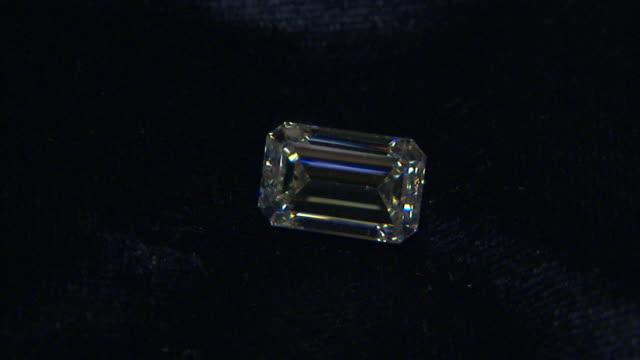light reflects off a diamond on a piece of velvet. - diamond gemstone stock videos and b-roll footage