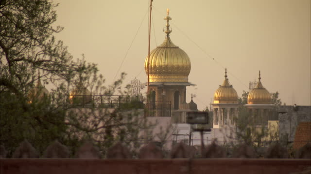 Light reflects off golden domes in Delhi.