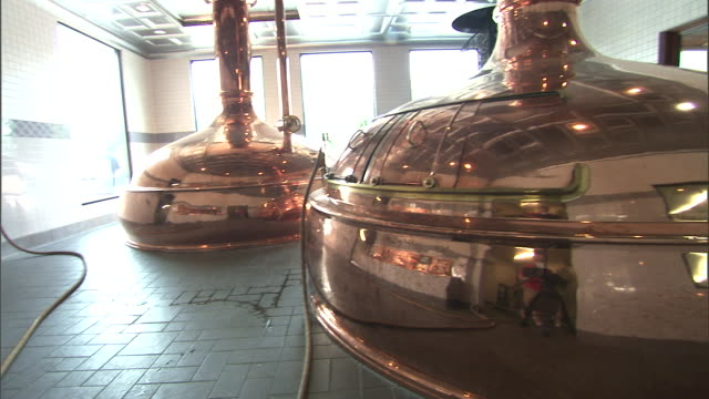 light reflects off two large vats next to a control panel in a brewery. - storage compartment stock videos & royalty-free footage
